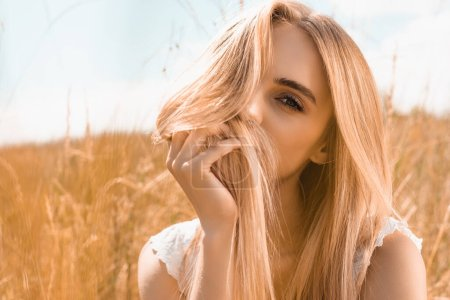 Photo for Young blonde woman obscuring face with hair while looking at camera against blue sky in field - Royalty Free Image