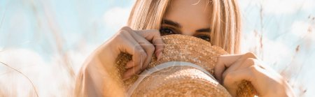 Photo for Selective focus of blonde woman obscuring face with straw hat against blue sky, website header - Royalty Free Image