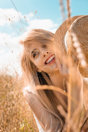 Photo for Selective focus of sensual blonde woman holding straw hat while looking away in grass - Royalty Free Image