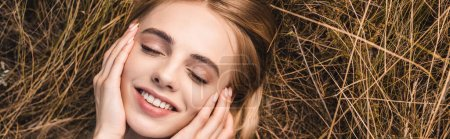 Photo for Panoramic shot of young blonde woman lying on green grass with closed eyes and touching face, top view - Royalty Free Image