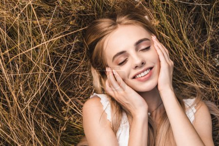 Photo for Top view of blonde woman touching face while lying on green grass with closed eyes - Royalty Free Image