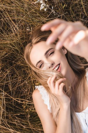 Photo for Selective focus of excited blonde woman touching hair and looking at camera while lying on grass with raised hand, top view - Royalty Free Image