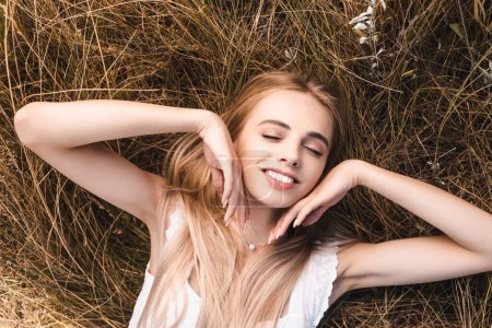 top view of sensual blonde woman touching face while lying on green grass with closed eyes