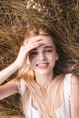 Photo for Top view of excited blonde woman touching forehead and looking at camera while lying on green grass - Royalty Free Image