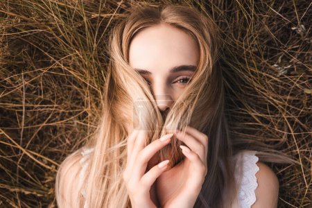 Photo for Top view of young blonde woman obscuring face with hair while lying on grass and looking at camera - Royalty Free Image
