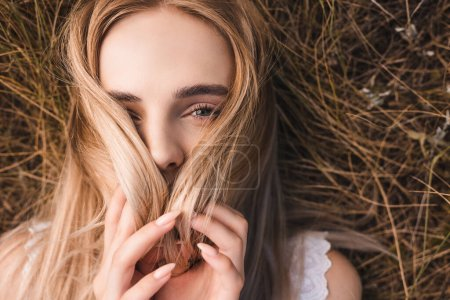 Photo for Top view of young blonde woman looking at camera while lying on green grass and obscuring face with hair - Royalty Free Image