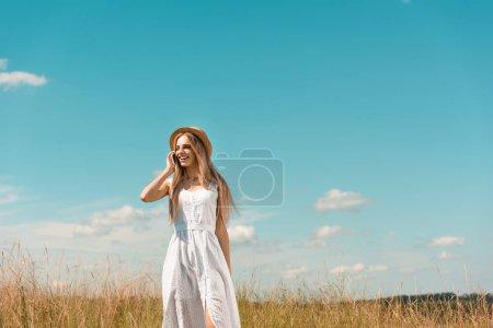 Photo pour Femme blonde élégante en robe blanche et chapeau de paille parler sur smartphone dans la prairie contre le ciel bleu - image libre de droit