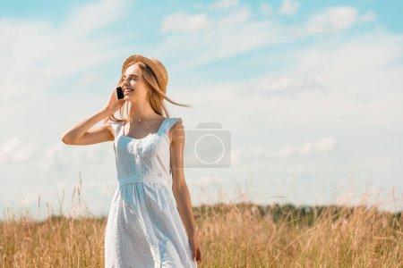 Photo pour Jeune femme en robe blanche et chapeau de paille parlant sur smartphone tout en se tenant dans le champ avec les yeux fermés - image libre de droit