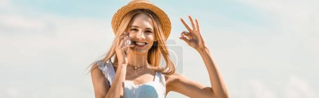 horizontal image of blonde woman in straw hat showing okay gesture while talking on smartphone against blue sky