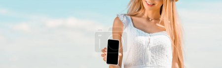 partial view of blonde woman showing smartphone with blank screen against blue sky, website header