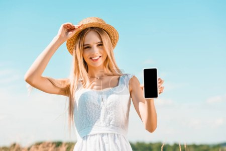 young blonde woman in white dress touching straw hat while showing smartphone with blank screen against blue sky
