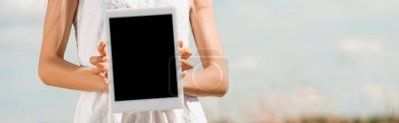 cropped view of woman showing digital tablet with blank screen against blue sky, horizontal image