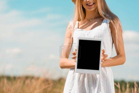 vue partielle de la jeune femme en robe blanche montrant tablette numérique avec écran blanc