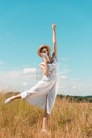 Photo pour Excitée femme blonde en robe blanche parlant sur tablette numérique tout en se tenant sur une jambe avec la main levée contre le ciel bleu - image libre de droit