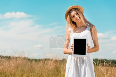 Photo for Blonde woman in straw hat and white dress showing digital tablet with blank screen while standing in filed - Royalty Free Image