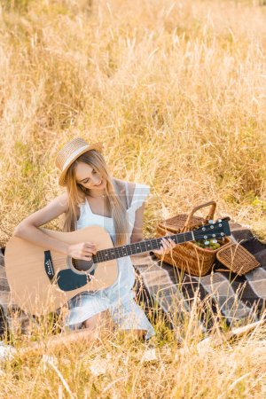 high angle view of blonde woman in white dress and straw hat playing acoustic guitar on blanket in field, selective focus