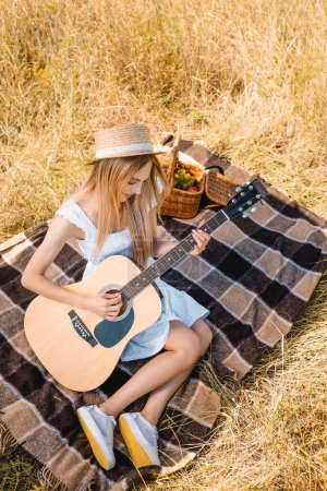 high angle view of blonde woman in white dress and straw hat sitting on plaid blanket and playing acoustic guitar