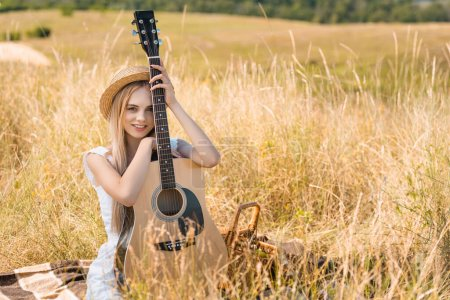 selective focus of blonde woman in summer outfit and straw hat sitting on blanket with acoustic guitar and looking at camera