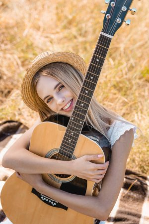 high angle view of blonde woman in straw hat sitting on blanket in field with acoustic guitar
