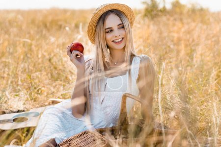 Photo for Selective focus of woman in white dress and straw hat holding ripe apple while sitting in field - Royalty Free Image