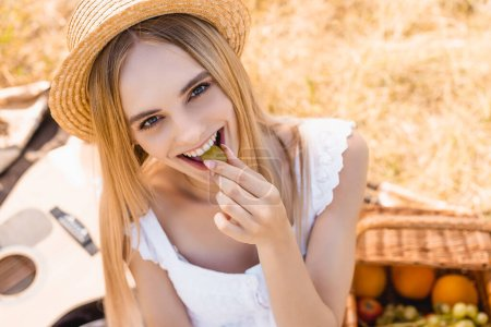 high angle view of blonde woman in straw hat eating ripe grape and looking at camera on picnic in field