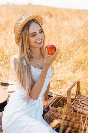 Photo for Selective focus of blonde woman in straw hat and white dress sitting on blanket near wicker basket and holding ripe apple - Royalty Free Image