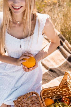 Ausgeschnittene Ansicht einer Frau im weißen Kleid, die orange hält, während sie auf einer Decke in der Nähe von Weidenkorb sitzt