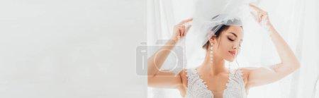 Foto de Cosecha panorámica de novia en vestido de novia y pendientes de perlas sosteniendo velo cerca de tela blanca - Imagen libre de derechos