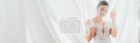 Photo pour Récolte horizontale de mariée en robe de mariée et voile regardant la caméra près de rideaux blancs - image libre de droit