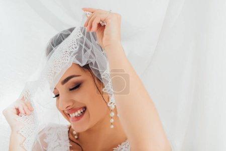 Photo pour Concentration sélective de la mariée en boucles d'oreilles perle tenant voile de dentelle près de tissu blanc - image libre de droit