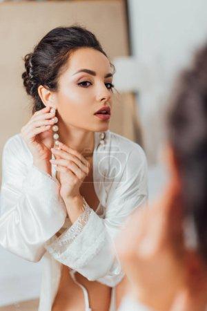 Photo pour Concentration sélective de la mariée en robe de soie portant boucle d'oreille perle près du miroir - image libre de droit