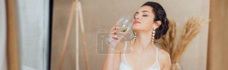 Foto de Foto panorámica de novia en sujetador y pendientes de perlas sosteniendo copa de vino en casa - Imagen libre de derechos