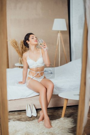 Photo pour Concentration sélective de la mariée en sous-vêtements tenant un verre de vin tout en étant assis sur le lit - image libre de droit