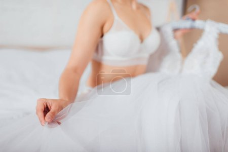 Ausgeschnittene Ansicht der Braut im BH berührt Brautkleid zu Hause