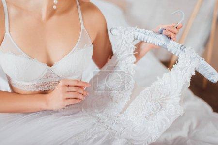 Photo pour Vue recadrée de la mariée en soutien-gorge en dentelle tenant robe de mariée blanche sur cintre dans la chambre - image libre de droit