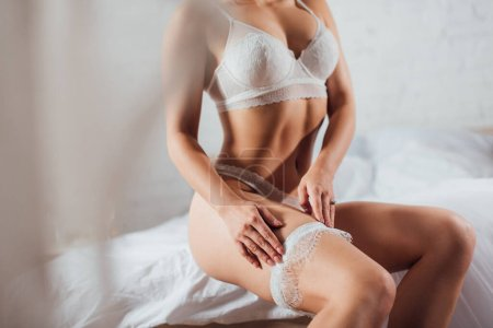 Photo pour Vue recadrée de la femme sensuelle en lingerie portant jarretière de mariage sur le lit - image libre de droit