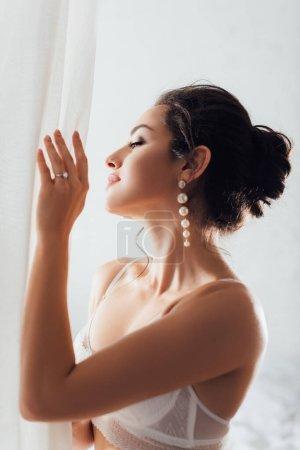 Photo pour Concentration sélective de la mariée brune en soutien-gorge et boucles d'oreilles perle touchant rideau blanc à la maison - image libre de droit