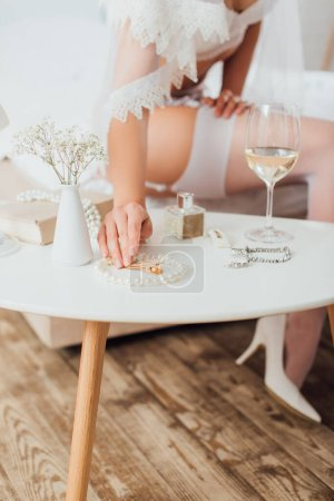 Photo for Selective focus of bride in bra and veil touching accessories near wine and perfume on coffee table - Royalty Free Image