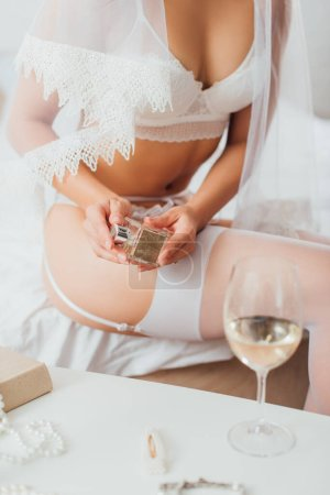 Photo for Cropped view of bride in lingerie and veil holding bottle of perfume near glass of wine on coffee table - Royalty Free Image