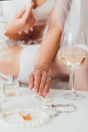 Foto de Vista recortada de la novia en velo y lencería tocando horquilla de perlas cerca de copa de vino en la mesa de café - Imagen libre de derechos