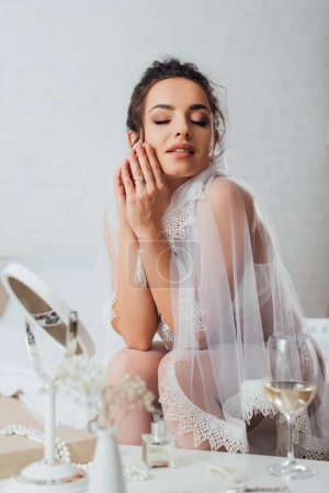 Photo for Selective focus of young bride in bra and veil sitting on bed near glass of wine, mirror and perfume on coffee table - Royalty Free Image