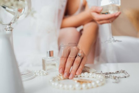Photo for Cropped view of bride touching pearl necklace and holding glass of wine at home - Royalty Free Image