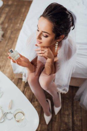 Photo pour Vue aérienne de la mariée en voile tenant un flacon de parfum assis sur le lit - image libre de droit