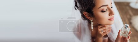 Photo for Horizontal crop of bride in veil holding bottle of perfume on bed - Royalty Free Image