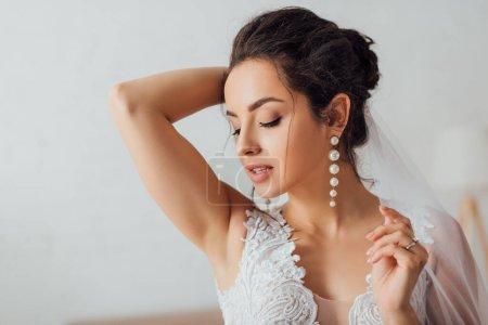 Photo pour Concentration sélective de la mariée brune en dentelle robe de mariée touchant voile - image libre de droit