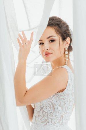 Photo pour Brunette mariée en dentelle robe de mariée en regardant la caméra tout en touchant les rideaux - image libre de droit