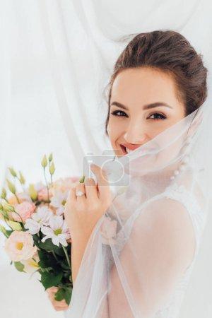Photo pour Jeune mariée tenant voile et bouquet tout en regardant la caméra près des rideaux - image libre de droit