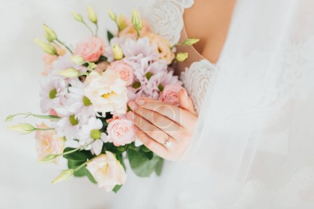 Photo for Cropped view of bride in wedding dress and veil holding floral bouquet - Royalty Free Image