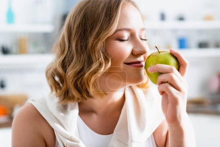 Photo for Young woman with closed eyes smelling green apple - Royalty Free Image