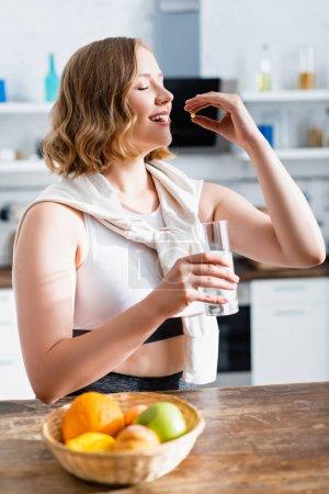 Photo pour Jeune femme prenant la pilule et tenant un verre d'eau près des fruits - image libre de droit